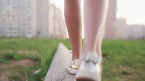 Close-up legs of little girl walking on concrete log on city wasteland stock footage