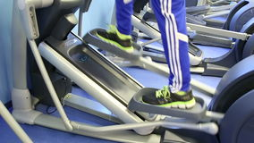 Close up of legs on lliptical fitness equipment stock footage
