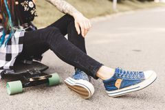 Close-up of legs and longboard standing on asphalt stock photography