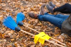 Close-up of the legs of a man and a girl sitting on the ground, next to lie two brooms and gloves. stock image