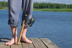 Close-up, legs of a man, near spinning for fishing, on a background of blue lake stock images