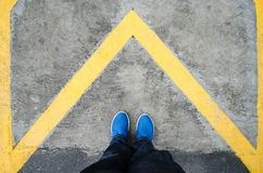 Close up on the legs of a man standing on a yellow triangle in the shape of an arrow, man standing on an arrow in a forward direct stock photo