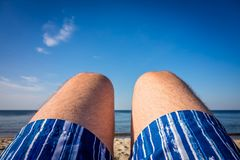 Mens legs on the beach. Close up of a legs of a man wearing blue shorts and lying on the beach in summer stock image
