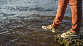 Close-up of legs of a man who takes a step into the river. Close-up of legs of a man who takes a step from stone into the river, summer evening royalty free stock photo