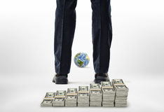 Close-up legs with packs of dollars and small globe. Royalty Free Stock Photo