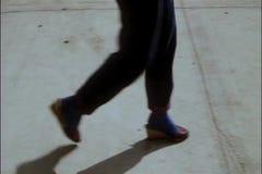 Close-up legs of people walking on sidewalk stock footage