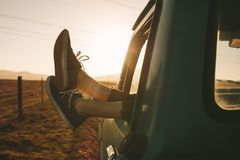 Close up of legs hanging out of a car on highway. Close up of legs of a relaxing woman hanging out from car on a highway in country side. Legs hanging out from Stock Photo