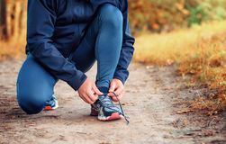 Close up a legs of runner in a black sports leggins and sneakers. Ties laces on a  path  on the  yellow autumn forest Royalty Free Stock Image