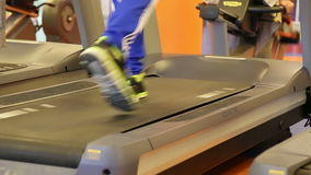 Close up of legs running on a treadmill in a gym stock footage