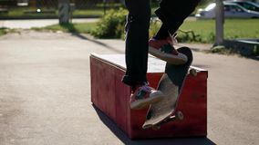 Close up of legs of skateboarder grinding over ledge in summer day outdoors. Teenager on board is sliding on barrier stock video footage