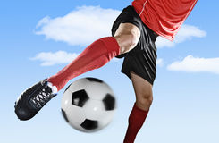Close up legs and soccer shoe of football player in action outdoors kicking ball isolated on blue sky Stock Photography