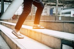 Close up legs of traveling people walking on stepping up stair i. N modern city. Sneakers and jeans elements. Business and travel concept. City lifestyle and stock images