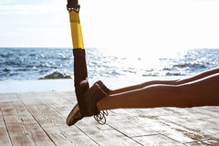 Close up of legs in trx, over sea background. Royalty Free Stock Photography