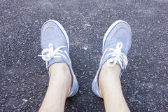Close up legs wearing blue sneakers Stock Images