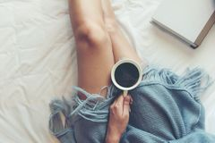 Free Close Up Legs Women On White Bed. Women Reading Book And Drinking Coffee In Morning Relax Mood In Winter Season. Stock Photo - 145579090