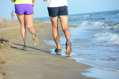 Close up legs of young couple man and woman running in the sand on the shore of beach by the sea during sunny summer holiday vacat Royalty Free Stock Photo