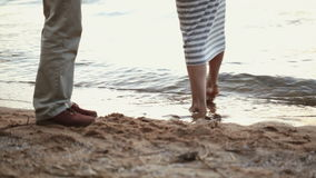 Close-up of legs of young couple on a sandy beach. The girl comes into water. stock video footage