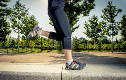 Close up legs of young man running in city park with trees on summer training session practicing sport healthy lifestyle concept Royalty Free Stock Photography