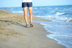 Close up legs of young man running in the sand on the shore of beach by the sea during sunny summer holiday vacat Royalty Free Stock Image