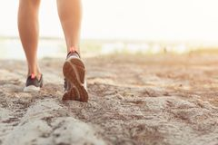 Close up of the legs of a young woman who is running off road in a park stock image