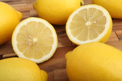 Close-up of lemons on wooden pad in the studio Stock Photos