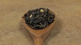Close-up, lepelomwenteling met een stapel van groene thee die op jute liggen stock footage