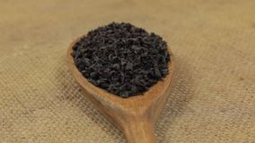 Close-up, lepelomwenteling met een stapel van zwarte thee die op jute liggen stock videobeelden