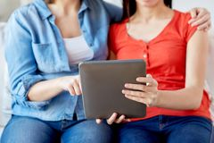 Close up of lesbian couple with tablet pc at home Royalty Free Stock Image