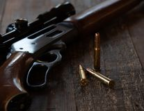 Close up lever action rifle and bullets. Close up lever action .30-30 caliber rifle and bullets with scope royalty free stock image