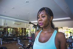 Close up lifestyle indoors portrait of young attractive and sweaty black afro American woman training hard at fitness club walking stock image
