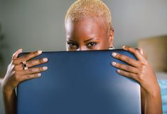 Close up lifestyle portrait of young classy attractive and happy black african american woman posing playful hiding behind laptop. Computer screen smiling Stock Photos
