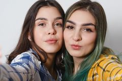 Close up lifestyle selfie portrait of two young positive woman having fun and making selfie, teenage hipster trendy clothes and royalty free stock photo