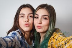 Close up lifestyle selfie portrait of two young positive woman having fun and making selfie, teenage hipster trendy clothes and stock photo