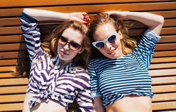 Close up lifestyle summer portrait of two girls friends relaxed and getting sunbathe, laying on the beach, wearing bright marine c Stock Image