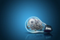 Close up of light bulb with gear mechanism inside. On dark blue background Royalty Free Stock Photography