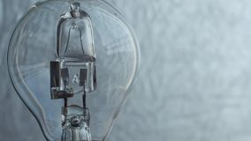 Close Up of light bulb over silver background. Electricity. stock footage