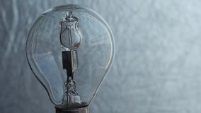 Close Up of light bulb over silver background. Electricity. stock video footage