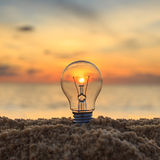 Close up light bulb on sunset beach Stock Photo