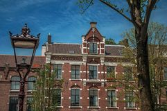 Close-up of light post, windows in old brick building facade and sunny blue sky in Amsterdam. Stock Image