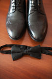 Close-up of lightened with natural light men's shoes and bow tie Royalty Free Stock Photo