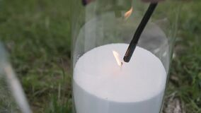 Close-up, lighter is used to set fire to wick of white loose candle in glass.