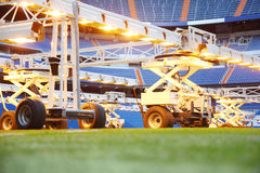 Close up of lighting system for growing grass at stadium. Close up of lighting system for growing grass at empty outdoor football stadium with blue seats Stock Image