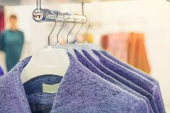 Close up lilac color coats on hangers in shop, butique. Make Outfit set. Shopping Mall. Shopper. Sales. Shopping Center. Selective. Focus. Space for text Royalty Free Stock Photos