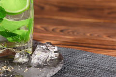 A close-up of a lime mojito. A refreshing green mojito with ice, mint and liquor. An alcoholic beverage on a wooden background. Royalty Free Stock Images