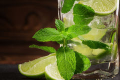 A close-up of a lime mojito. A refreshing green mojito with liquor, mint and ice. An alcoholic beverage on a wooden background. royalty free stock images