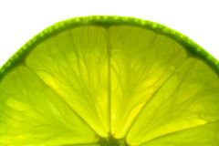 Close-up of lime slice. A part of a green lime slice, backlit and isolated on white background Royalty Free Stock Photos
