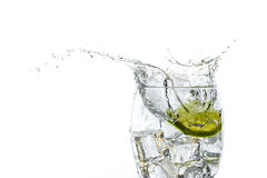 Close up of lime slice dropped in water glass. Stock Photo