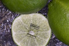 Close up on slice of lime with fresh limes with nutrition label. Close up of lime slice with fresh whole limes on granite with nutritional label Stock Photography