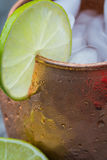 Close up of lime slice on moscow mule drink in copper cup. Copper mug with a lime slice hanging on the edge.  Ice cubes and condensation are also visible Stock Photos
