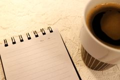 Closeup angled view of a blank A5 sized notebook and a cup of coffee royalty free stock image